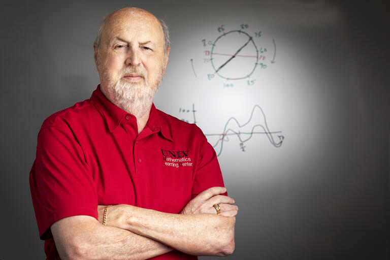 A portrait of Bill Speer, director of UNLV's Math Learning Center, standing in front of a white board.
