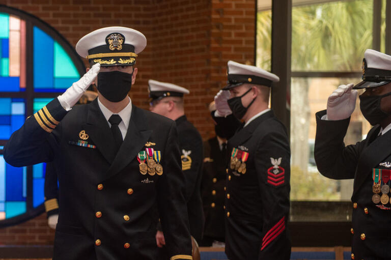 Navy Commander Stephen Col, facing camera in uniform and saluting