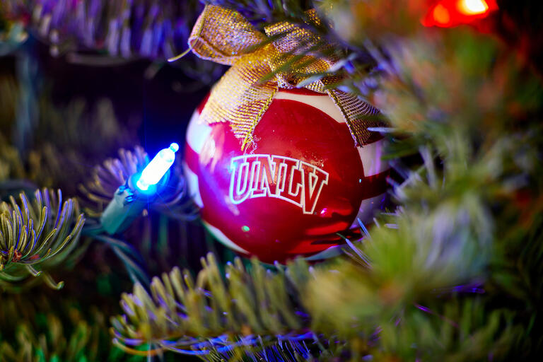 "Red ""UNLV"" Christmas ornament on tree"