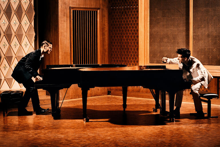 Andreas Kern and Paul Cibis look at each other from across a grand piano