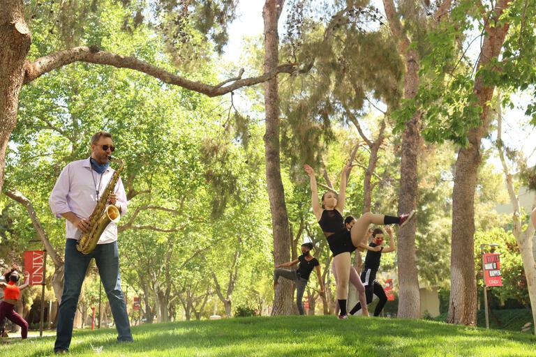 A man plays the saxophone while dancers gambol around him