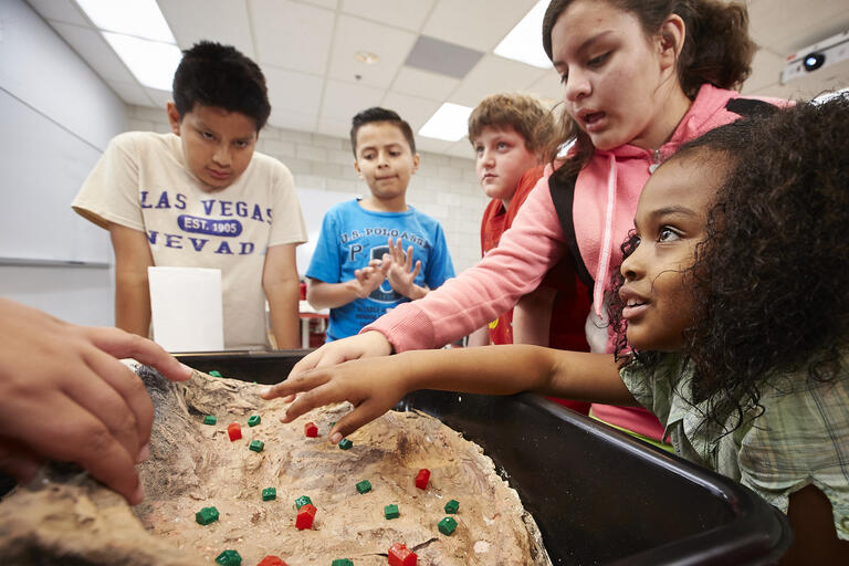 A group of five fifth graders partake in an experiment during UNLV's Rebel Science Camp.