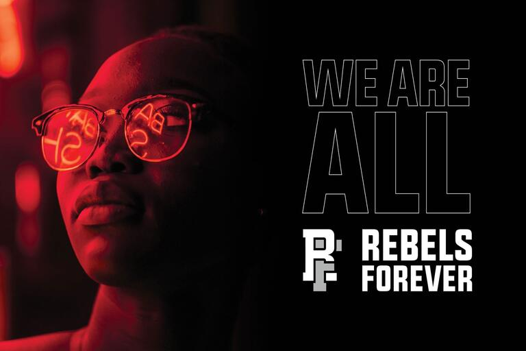 person with glasses looking into distance with Rebels Forever logo