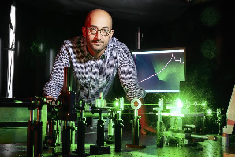 Physicist standing over table with green laser beams
