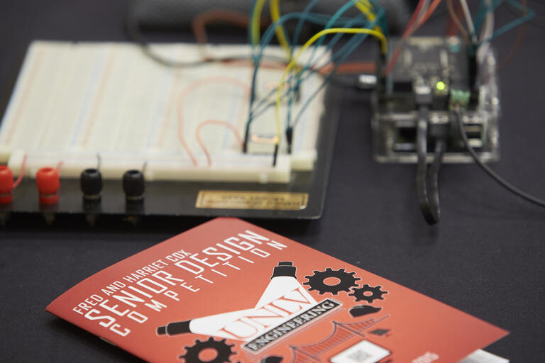 Red event program for Senior Design Competition with electrical device in background