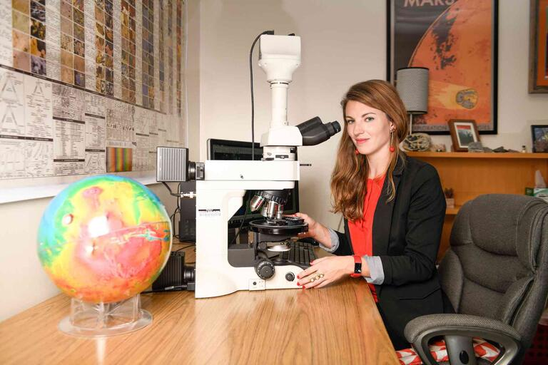 UNLV geoscientist Arya Udry sits in front of her microscope in her office