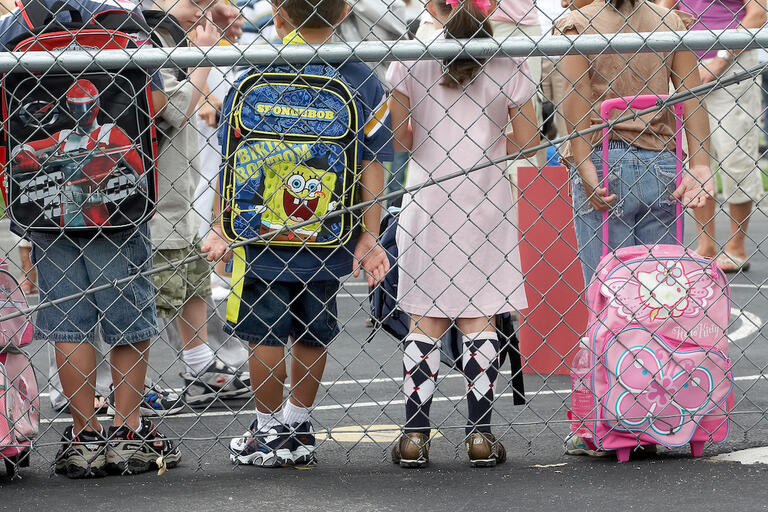 children standing on a playground with their backs to the camera and their backpacks visible