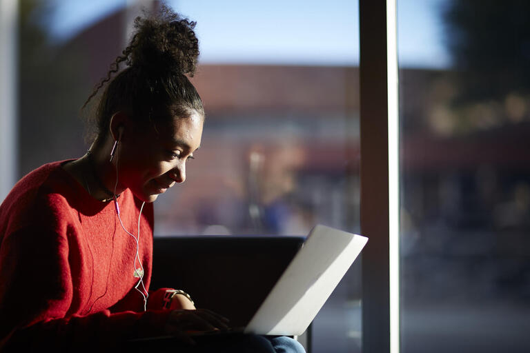 girl on computer with earbuds