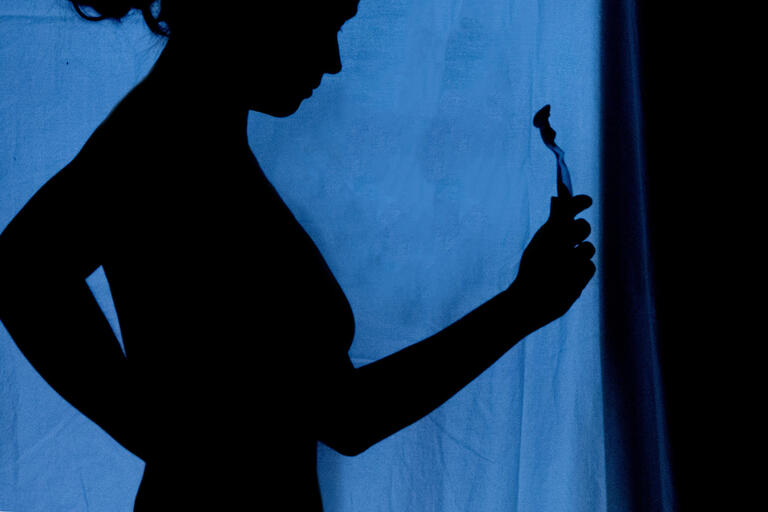 silhouette of woman holding razor against blue background