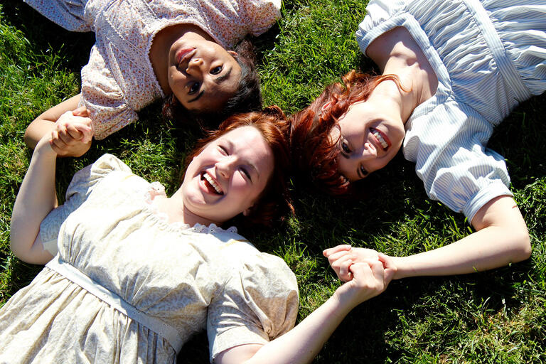 Christina Harvey, Therese Anderberg, and Alexandra Ralph lay in the grass, holding hands