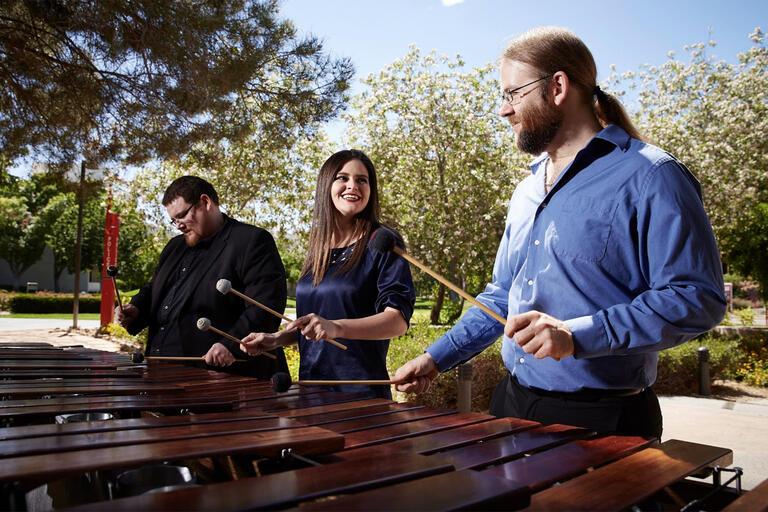three people playing marimba
