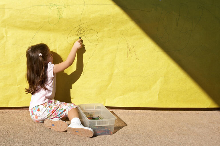 girl coloring on yellow paper
