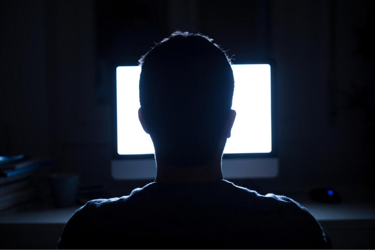 Silhouette of man sitting in a dark room in front of a glowing computer screen.