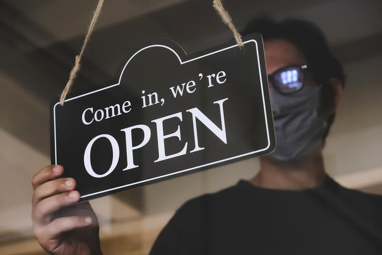 """man wearing mask holds an """"open"""" business sign"""