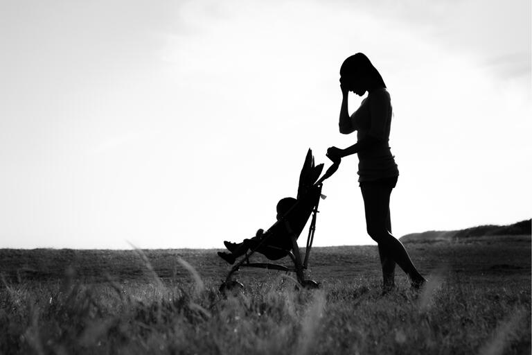 An silhouette image of a mother pushing her child in a stroller.