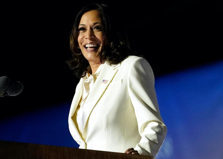 Kamala Harris wearing a white suit while giving her victory speech