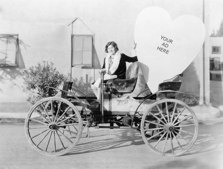 1910s woman sitting in vintage car with large cardboard heart that reads: Your Ad Here