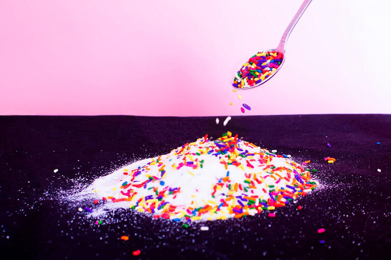 spoon pours candy sprinkles atop pile of white sugar