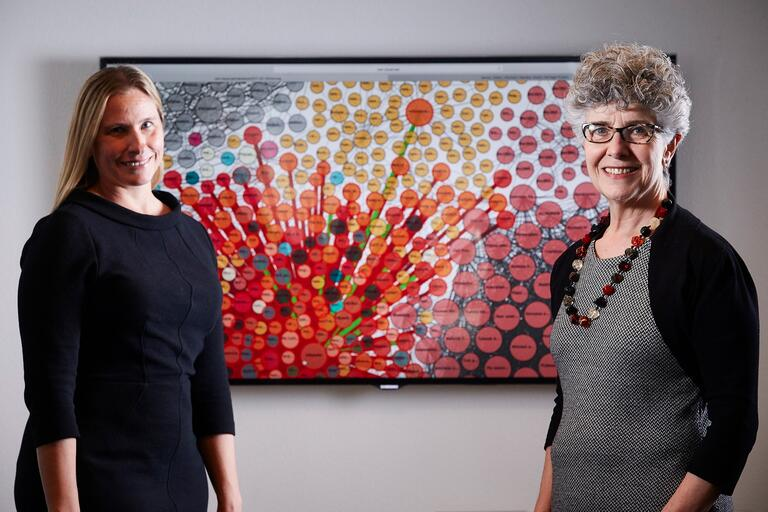 Cory Lampert and Silvia Southwick pose in front of a colorful data display