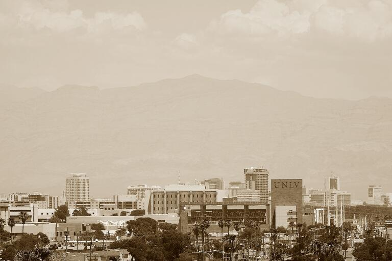 Sepia tone photo of the U.N.L.V. campus with mountains and clouds in the background