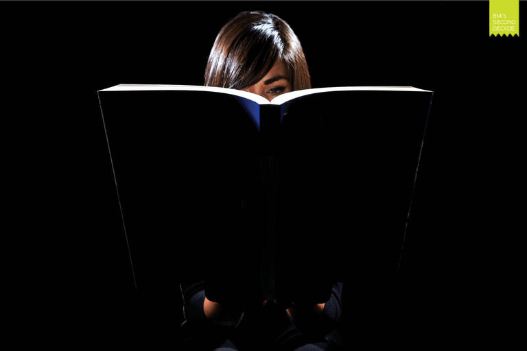 girl reads a book under a light