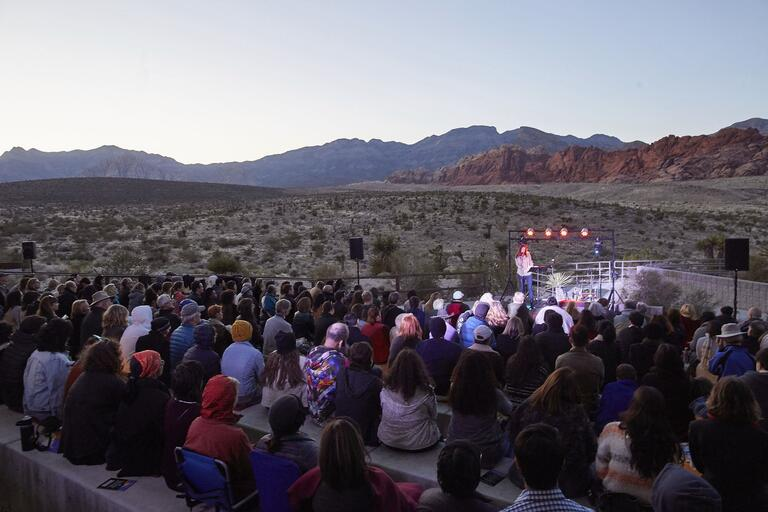 Person speaking in front of crowd at Red Rock Canyon