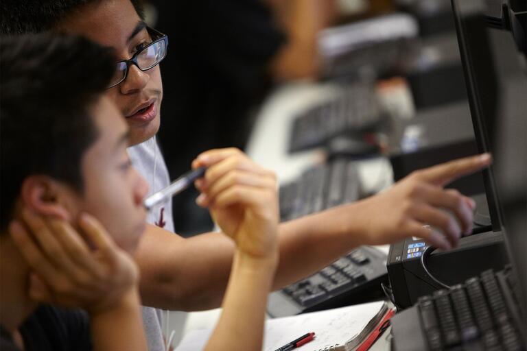 Student talk while looking at a computer monitor