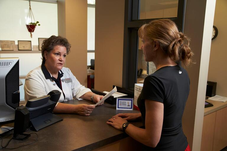 Student speaks with receptionist at front desk