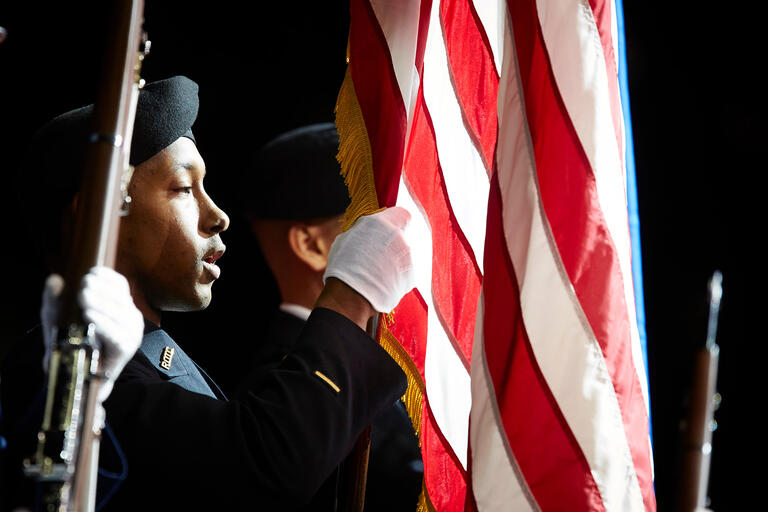 An army R.O.T.C. student in uniform holding the American flag.