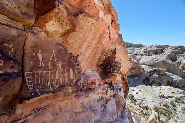 Petroglyph engravings in the side of a rock formation in the desert.