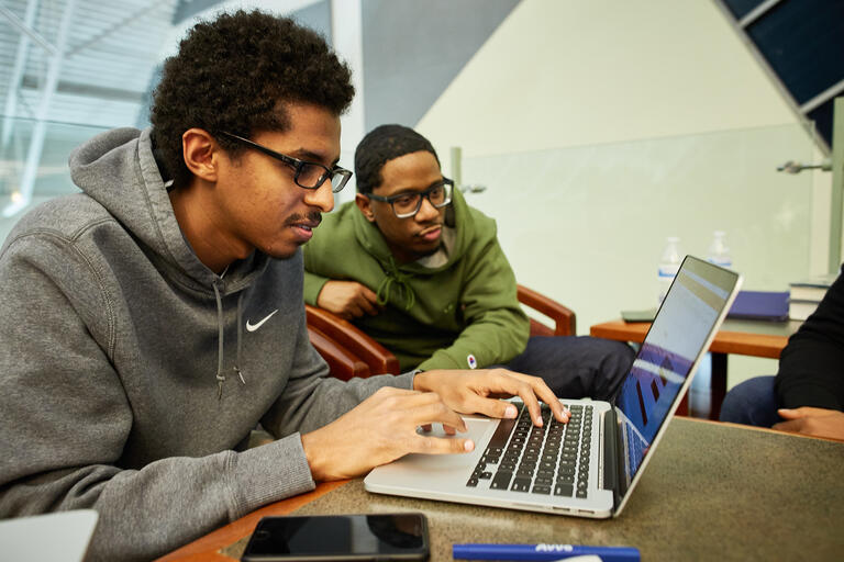 Two men working together at a computer.