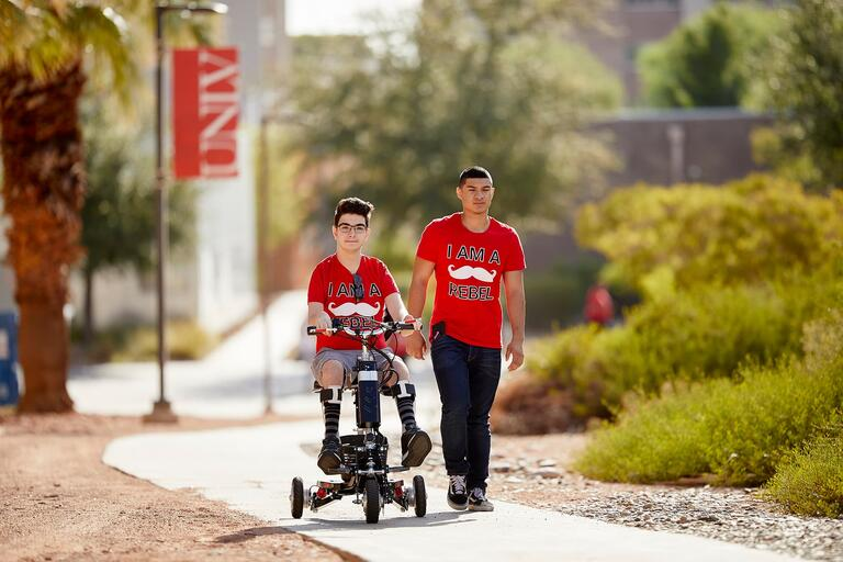 UNLV students going through campus one student rides a scooter while the other walks