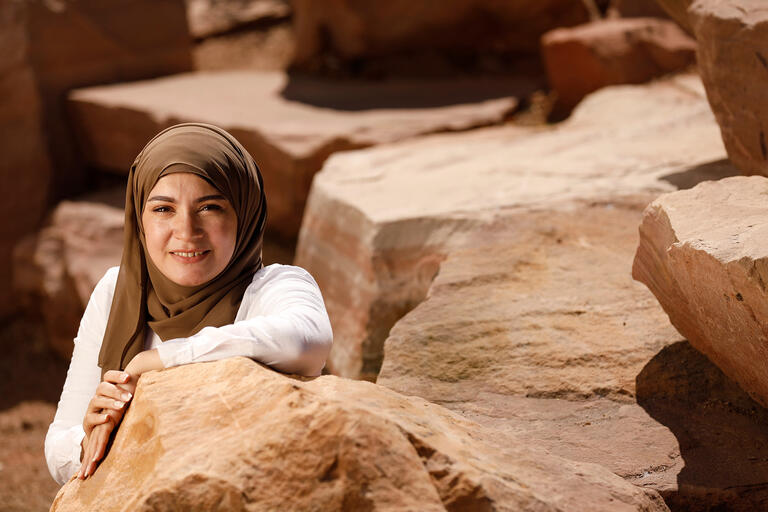 A woman wearing a veil over her head sitting among different rock formations.