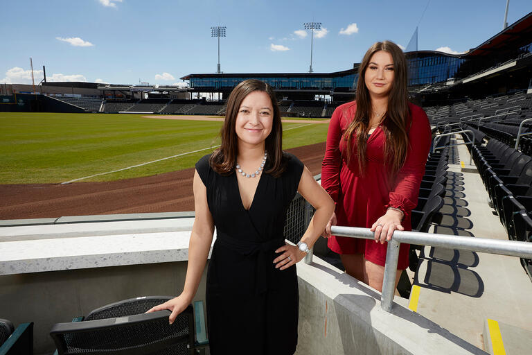 Two women in business attire standing in the box seats of a new baseball stadium.