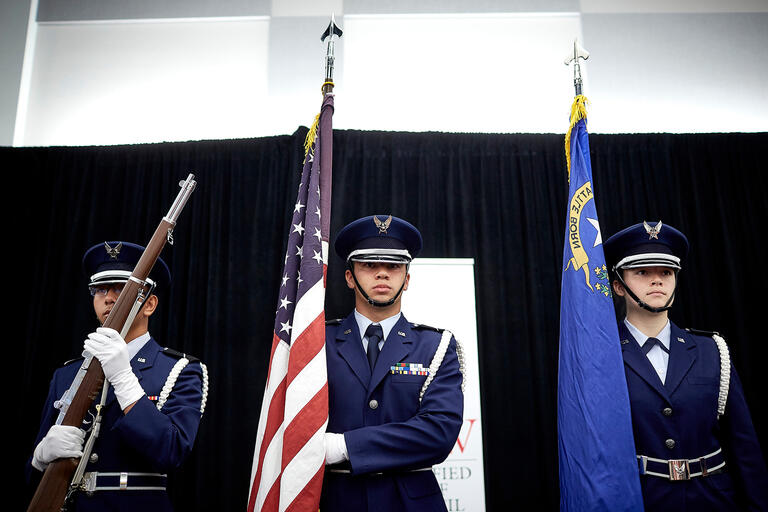 Air Force R.O.T.C. students in uniform holding flags.