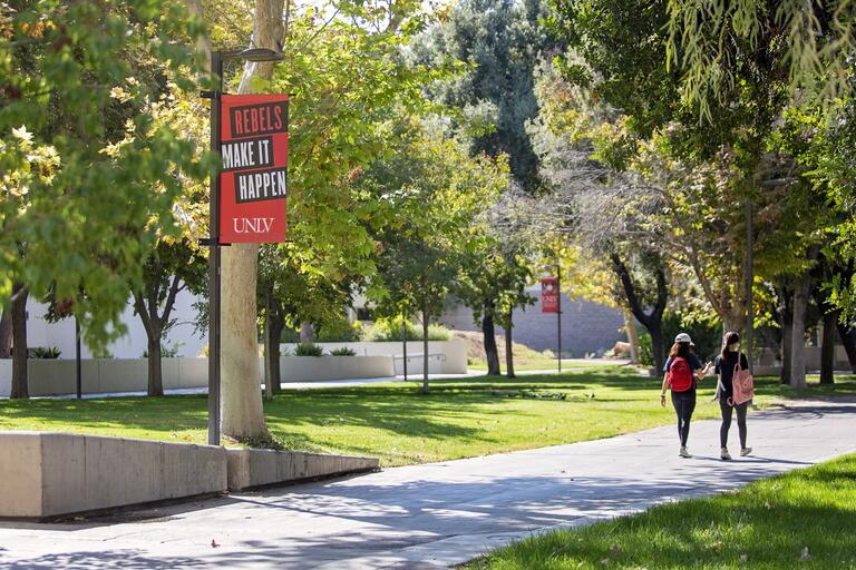 UNLV walkway with students walking on sidewalk, passing sign that says Rebels Make It Happen