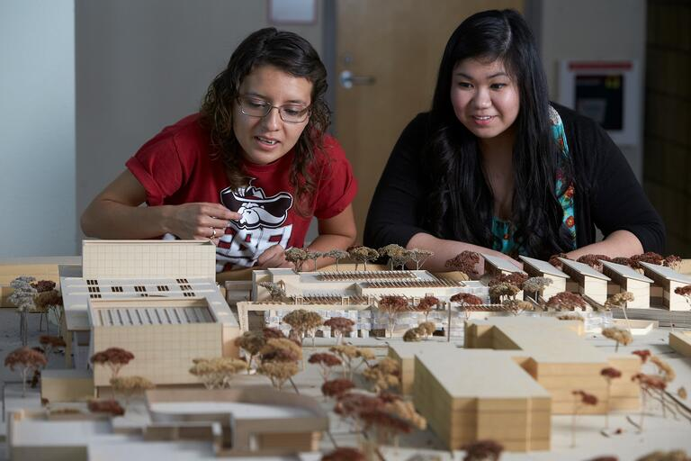 Two students look over building models