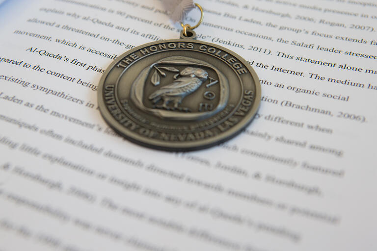 An Honors College medallion laid on top of an open textbook