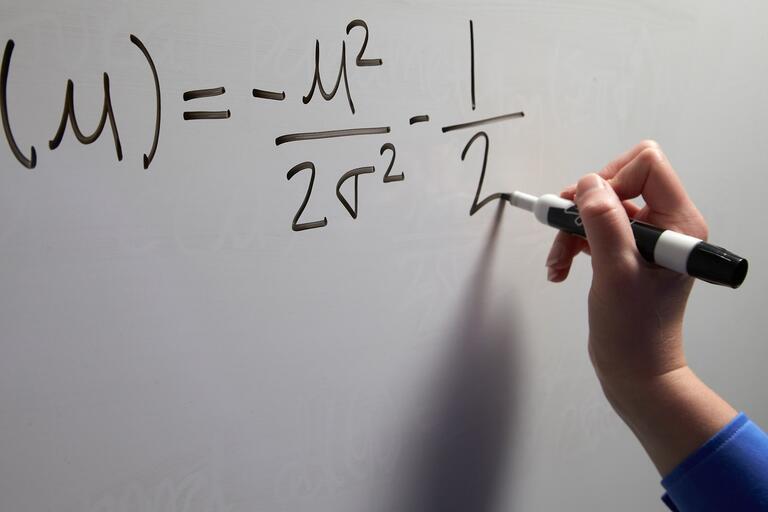 Closeup hand writing an equation on a white board