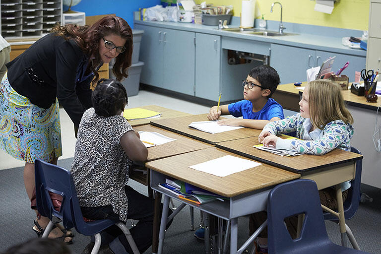 Female teacher bending over to talk to three elementary-aged children sitting at their desks