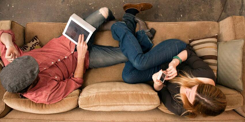Couple lounging on couch with digital devices