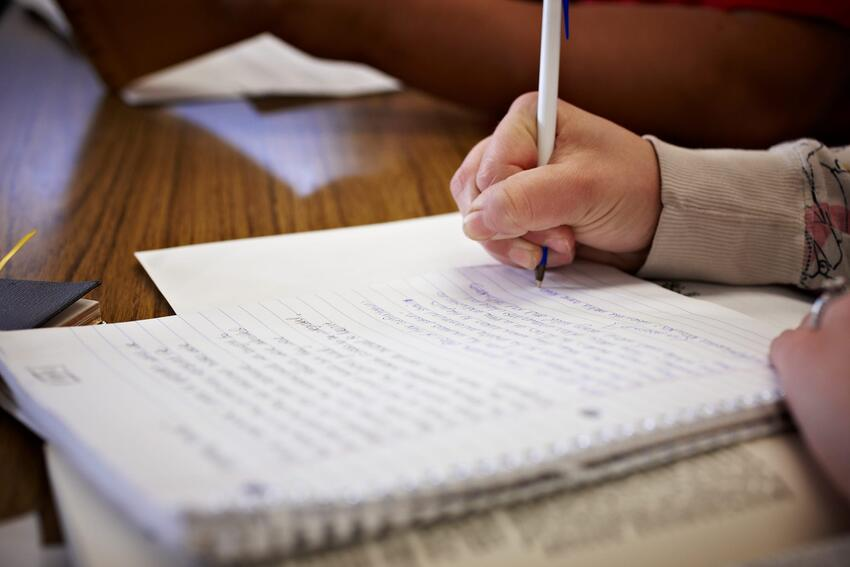 Closeup of a student writing in a notebook