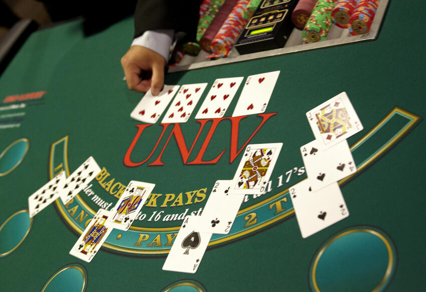 Playing cards at a game table that has U.N.L.V. etched in the green felt.