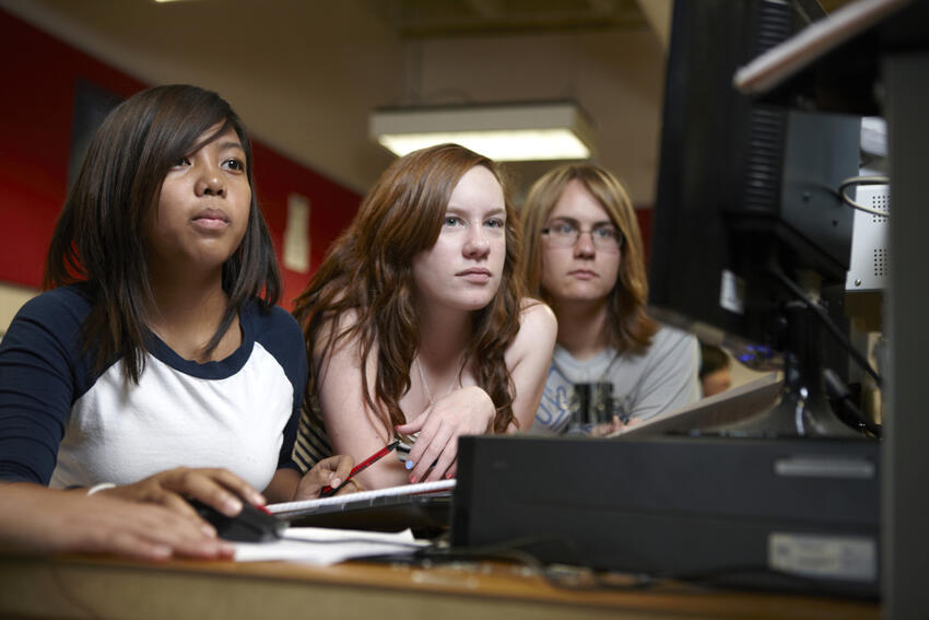 Three students working on a computer