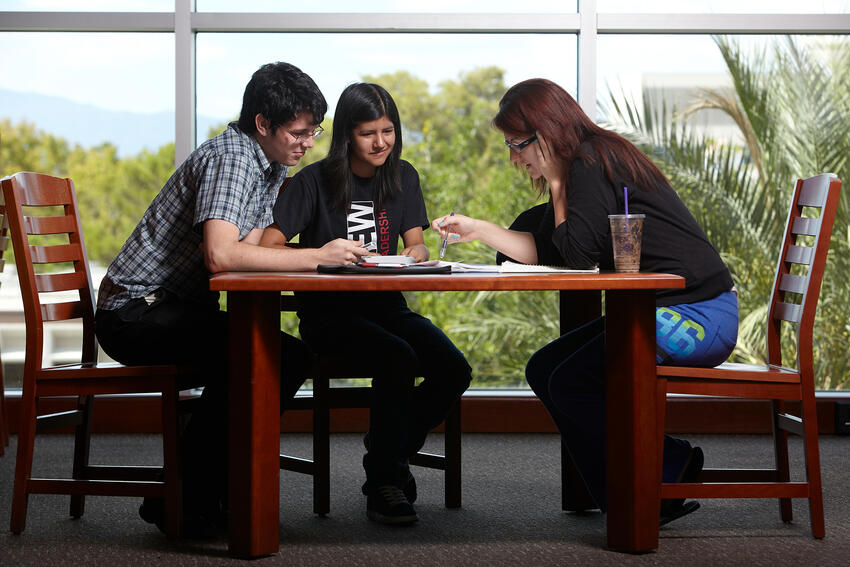 Three students study together at table in library