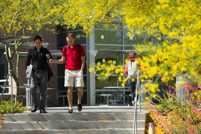 Two students bump fists while walking down steps outside of the Student Recreation and Wellness Center building