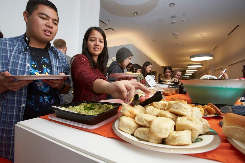 Students serve food on their plates at Thanksgiving dinner