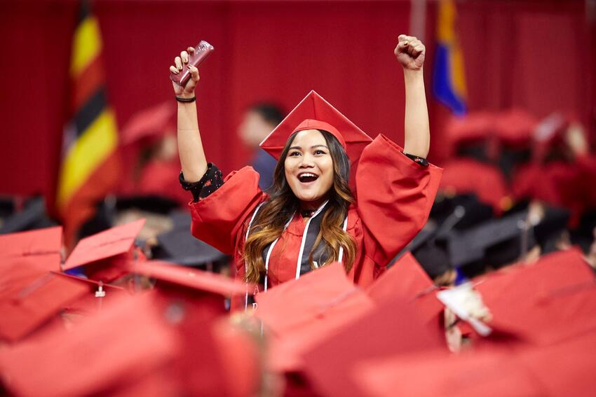 Student celebrates with her hands in the air during graduation ceremony