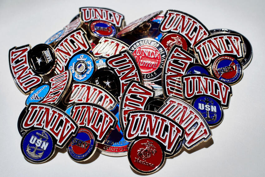 A pile of UNLV pins with various military branch emblems.