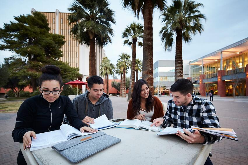 Four students study outside of the Student Union